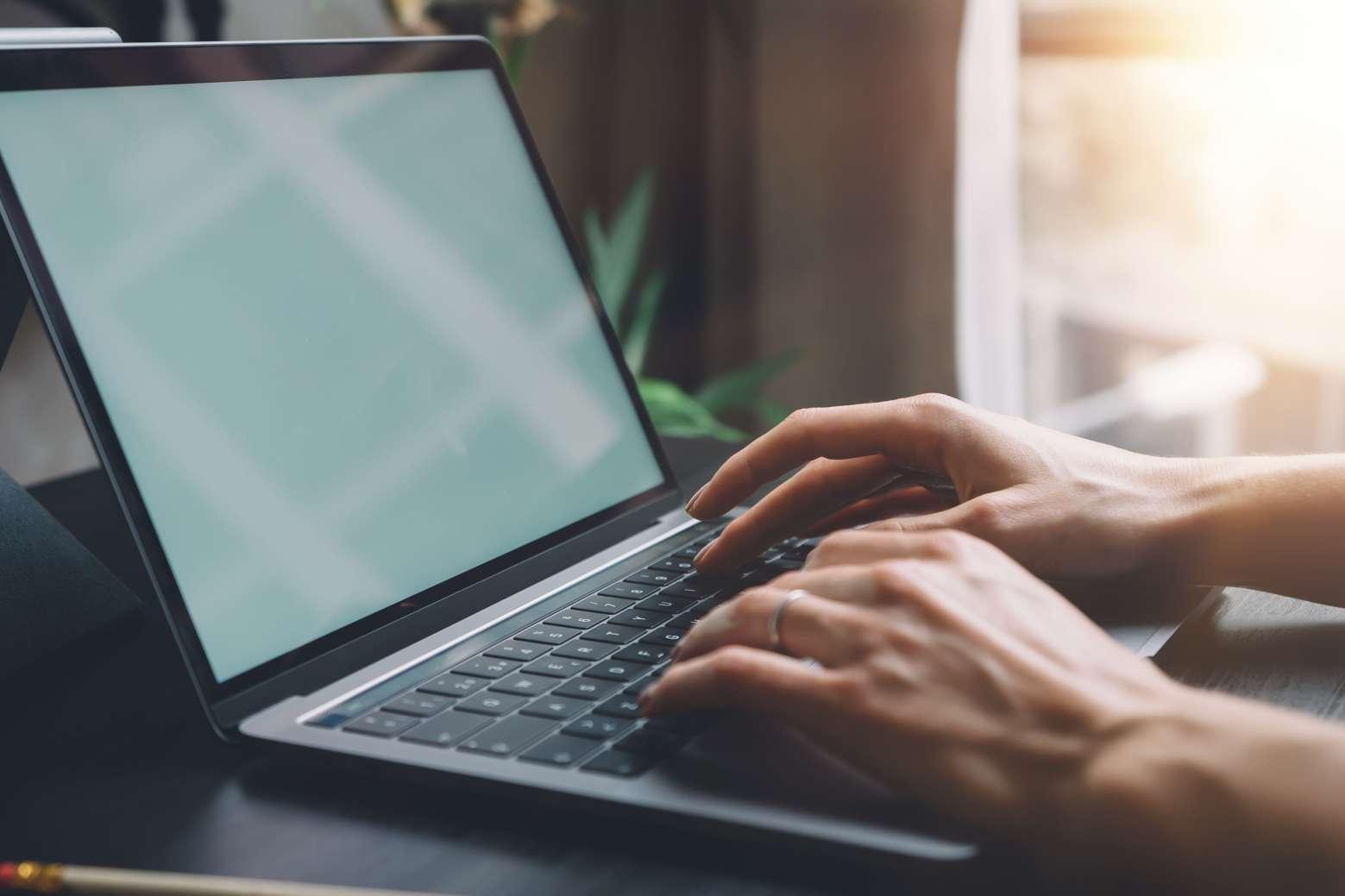 Deux mains tapant sur un ordinateur portable lors de la saisie d'une annonce légale